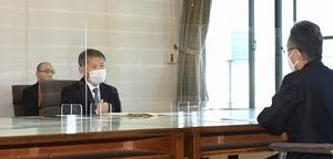 運転40年を超える福井県内の原発再稼働について、杉本達治知事(右)に理解と協力を求める保坂伸長官=10月16日、福井県庁