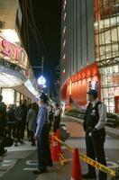路上で2人が倒れていた現場付近を規制する警察官ら=23日午後7時8分、大阪市