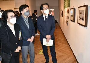 24日、韓国・釜山で開かれた写真展を訪れた李秀賢さんの母・辛潤賛さん(左)と丸山浩平・駐釜山総領事(右)ら(共同)
