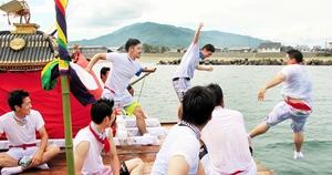 みこしに入った弁財天を喜ばせるため、船上で海へ落とし合う若者たち=8日、福井県美浜町の沿岸