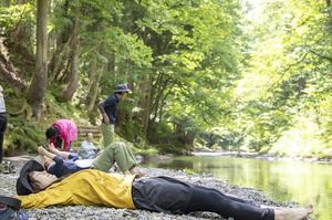 裸足になって川沿いに寝そべりアーシング体験する参加者=2019年6月、福井県池田町