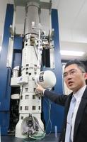 高さ約3メートルの新開発の電子顕微鏡を説明する柴田直哉東京大教授=22日、東京都文京区