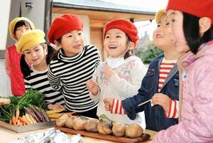 焼きたてのジャガイモに「いいにおい」と笑顔を見せる子どもたち=2月14日、福井県あわら市北潟