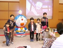 ドラえもんのオブジェと一緒に記念写真に納まる子どもたち=1月2日、福井県勝山市の県立恐竜博物館