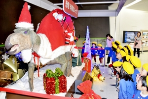 サンタ姿の恐竜を見つめる子どもたち=11月30日、福井県勝山市の福井県立恐竜博物館