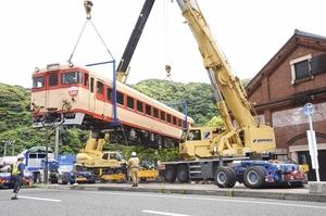 クレーンを使って慎重に設置される気動車「キハ28形」=5月19日、福井県敦賀市金ケ崎町