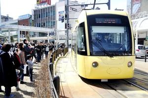 多くの鉄道ファンがカメラを構える中、福井鉄道福井駅停留場に一日限定で乗り入れるえちぜん鉄道のキーボ=24日、福井市中央1丁目