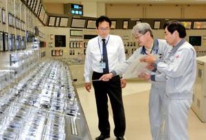 シミュレーター室で人為ミスの原因と対策について説明を受ける渕上隆信市長(左)=6日、福井県敦賀市の高速増殖炉もんじゅ