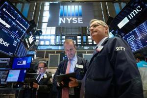 ニューヨーク証券取引所のトレーダーたち=16日(ロイター=共同)