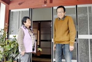 農家民宿「ざくろの宿」の前で、近所の人と交流する柑本修さん(右)=福井県鯖江市