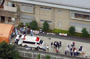 刃物を持った男が侵入し、多数の死傷者が出た障害者施設「津久井やまゆり園」で対応する救急隊員や関係者=26日午前7時10分、相模原市緑区(共同通信社ヘリから)