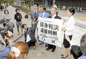 「1票の格差」訴訟の判決を受け、「保身判決」などと書かれた紙を掲げる原告側=17日、名古屋高裁金沢支部前