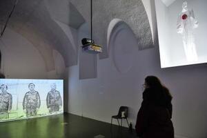 5日、ウィーンの芸術展「ジャパン・アンリミテッド」で展示された作品。東京電力幹部の謝罪会見を基にした動画(左)や日の丸の形に血が浮かぶ放射線防護服のようなオブジェ(右上)(共同)