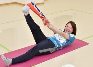 タオルを使ったストレッチを行う福井丸岡RUCKの前田海羽選手。伸ばした足先に掛けて引っ張り、もも裏とふくらはぎに効かせる