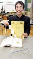 考案したブックストッパーと特許証を手に笑顔を見せる天谷武琉さん=16日、福井市の高志高