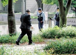 強盗事件発生を受け、隣の幾久公園で草むらを調べる捜査員=5月4日午前7時25分ごろ、福井県福井市大宮2丁目