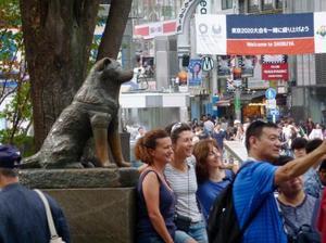忠犬ハチ公像と一緒に写真に収まる訪日客たち=東京都渋谷区