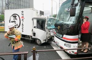 東京都港区新橋4丁目の交差点で起きた、トラック(左)や観光バス(右)が絡んだ事故現場=21日午前