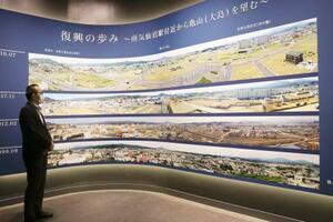 再開した宮城県気仙沼市の東日本大震災遺構・伝承館に新設されたパノラマ写真。左は佐藤克美館長=2日午前