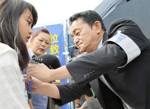 女の子にブルーリボンを付けてあげる地村保志さん(右)=8日、福井県小浜市川崎3丁目