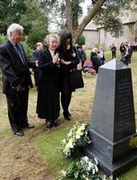 4日、英西部ウェールズのアングルで「平野丸」の慰霊碑に向かい祈りをささげる中村良子さん(左から2人目)ら(共同)