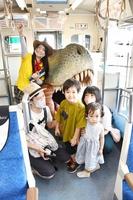 恐竜モニュメントをバックにアテンダント(左奥)と出発前に記念撮影する親子=7月23日、福井県福井市のえちぜん鉄道福井駅