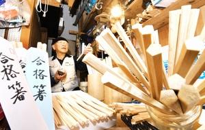 合格を願い五角形の箸に仕上げる元大工の尾崎専一さん=福井県福井市
