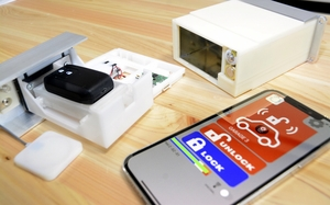 スマートキーを保管するケースと、車の施錠などを行うスマートフォン=福井県福井市の「システムデザイン」