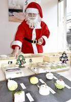 サンタクロースにふんし、クリスマス用和菓子を店頭で作っている谷川イリーナさん=12月23日、福井県小浜市一番町の伊勢屋