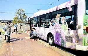 ちはやふるのラッピングバスと写真に納まる来場者=2日、福井県あわら市「aキューブ」