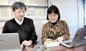 集計装置の開発に取り組む廣瀬さん(左)と葛城さん=福井県鯖江市役所