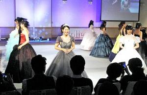 自作した華やかなドレスでステージに立つ啓新高ファッションデザイン科3年生=7日、福井市の福井商工会議所ビル