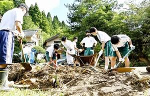 住宅の敷地内に流れ込んだ草木や泥を取り除く川西中学校の生徒ら=7月31日、福井県福井市荒谷町