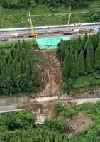 大分県九重町の大分自動車道(上)で起きた土砂崩れ現場。下は国道210号=9日午前11時33分(共同通信社ヘリから)