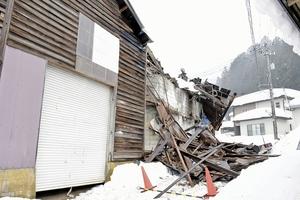 雪の重みで屋根や壁の一部が崩れた製紙所の工場=15日、福井県越前市