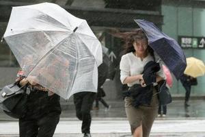 強い雨の中、風にあおられながら歩く人たち=21日午前、東京・丸の内