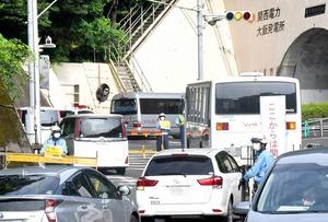 大飯原発のゲート付近に連なる作業員らを乗せた車両=7月20日午前7時35分ごろ、福井県おおい町大島