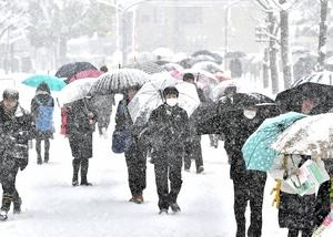 雪が激しく降る中、センター試験会場へ向かう受験生=13日午前8時5分ごろ、福井市の福井大文京キャンパス