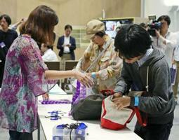 「表現の不自由展・その後」の展示再開にあたり、入場前に手荷物を預ける来場者(右)=8日午後、名古屋市(代表撮影)