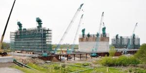 多くのクレーンが並び、巨大な橋脚が造られている九頭竜川橋の建設現場