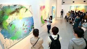 大宮エリーさん(中央)の解説を聞きながら作品を鑑賞する来場者=福井県あわら市の金津創作の森