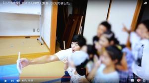 投稿した動画の中で、子どもたちと記念撮影するカズさん(左奥)