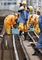 橋脚が傾きレールのゆがみが確認された、大阪府の大和川に架かる近鉄南大阪線の橋で復旧作業する作業員=25日午後