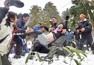 雪の斜面に放り投げられる男性=2月2日、福井県鯖江市尾花町の殿上山