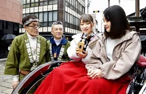コミュニケーションロボットと越前こぶし組の人力車に乗る女性客=3月20日、福井県大野市元町の七間通り
