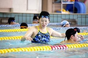 子どもたちに泳ぎ方を指導する金藤さん=3月17日、福井県おおい町フィットネスセンター「アクアマリン」