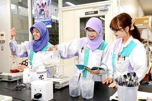 同じ職場の先輩(右)に染色の手順を習うアリン・インディアルニさん(左)とイク・オクタマ・クリスティさん=福井市の日華化学総合研究所