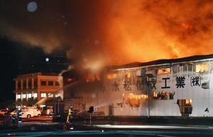 炎と煙が上がる「赤松化成工業」のプラスチック工場=16日午後6時50分、徳島県松茂町