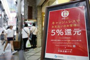 ポイント還元ができるキャッシュレス決済サービスの対象店舗に掲げられたポスター=2019年、大阪市