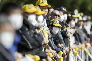 プロ野球・阪神のキャンプで、マスクを着け選手の練習を見つめるファン=2020年2月1日、沖縄県宜野座村